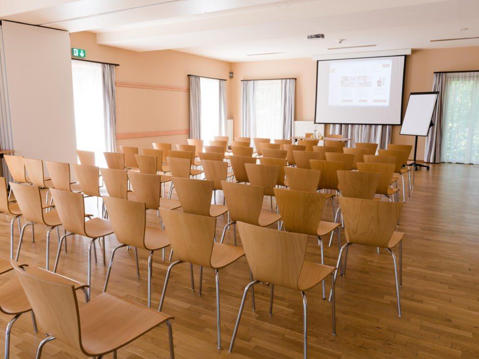 Sie sehen einen gut ausgestatteten Seminarraum im JUFA Hotel Fürstenfeld - Sport-Resort mit Reihenbestuhlung. JUFA Hotels bietet Ihnen den Ort für erfolgreiches Training in ungezwungener Atmosphäre für Vereine und Teams.