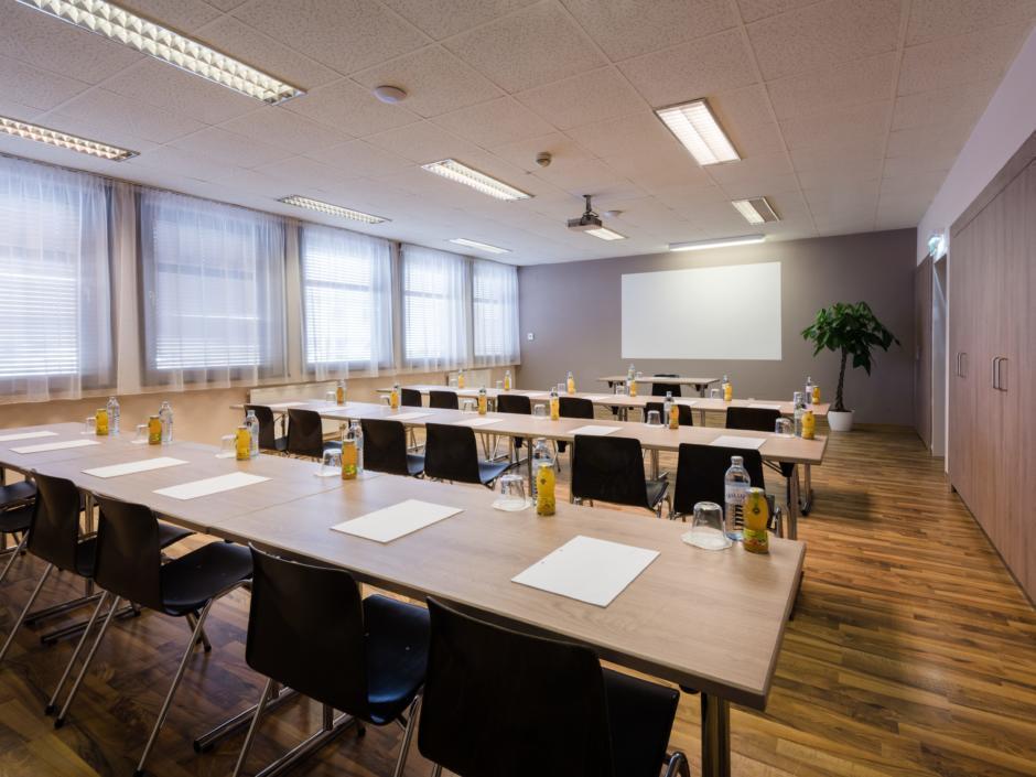 Sie sehen einen gut ausgestatteten Seminarraum im JUFA Hotel Graz-Süd mit Beamerwand und Reihenbestuhlung. JUFA Hotels bietet den Ort für erfolgreiche und kreative Seminare in abwechslungsreichen Regionen.