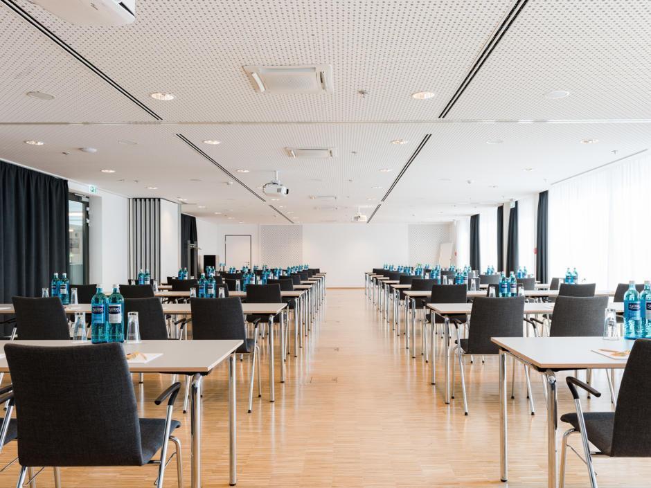 Sie sehen einen gut ausgestatteten Seminarraum im JUFA Hotel Hamburg HafenCity mit Reihenbestuhlung. JUFA Hotels bietet den Ort für erfolgreiche und kreative Seminare in abwechslungsreichen Regionen.