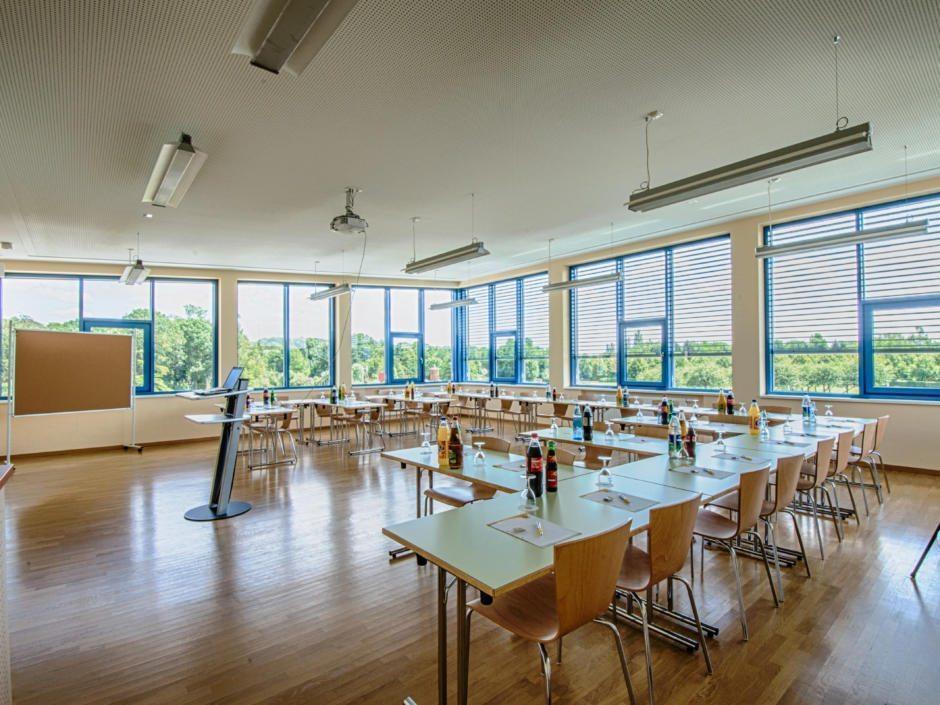 Gut ausgestatteter Seminarraum mit aufgestellten Tischen in U-Form im JUFA Hotel Jülich. Der Ort für kinderfreundlichen und erlebnisreichen Urlaub für die ganze Familie.
