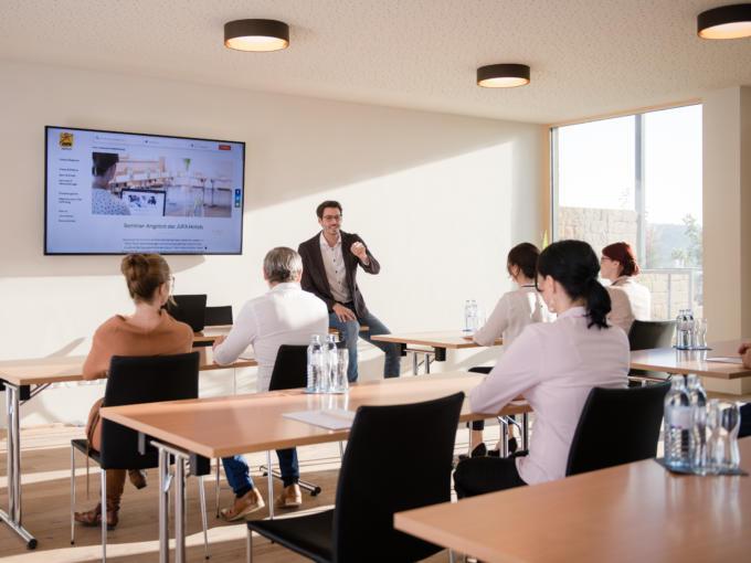 Sie sehen einen gut ausgestatteten Seminarraum im JUFA Hotel Neutal – Landerlebnis mit Seminargetränken. JUFA Hotels bietet den Ort für erfolgreiche und kreative Seminare in abwechslungsreichen Regionen.