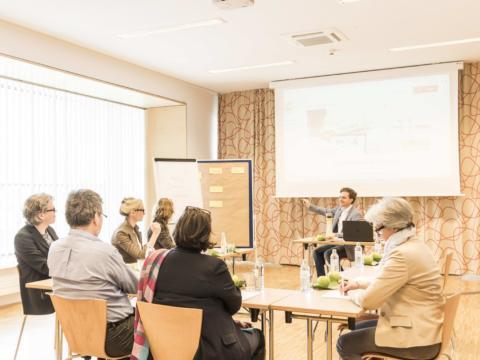 Modern ausgestatteter Seminarraum mit Seminarteilnehmern im JUFA Hotel Wien City. Der Ort für erlebnisreichen Städtetrip für die ganze Familie und der ideale Platz für Ihr Seminar.