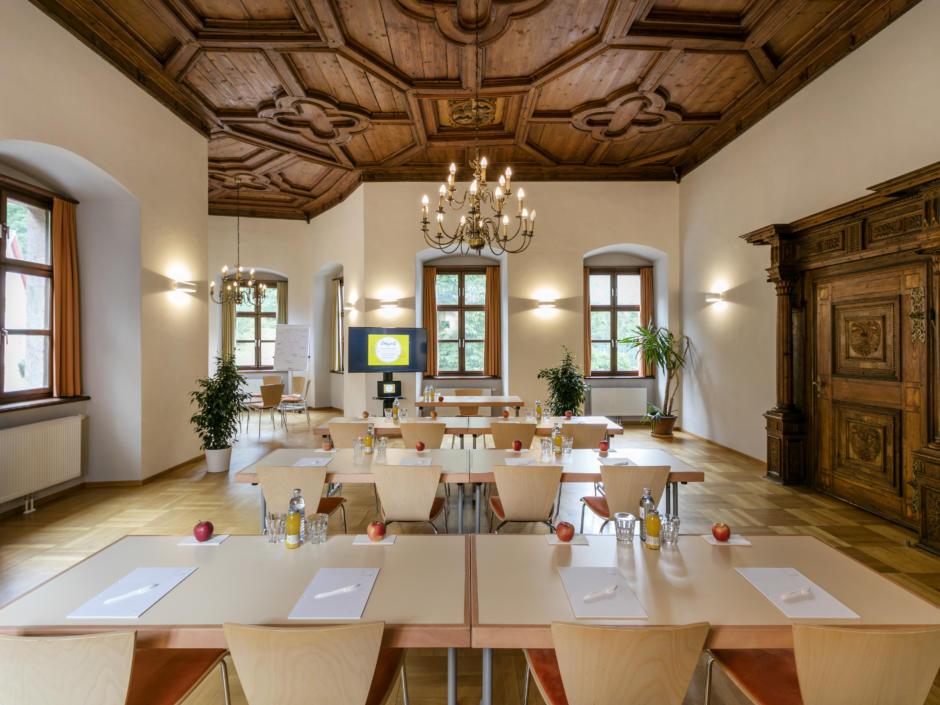 Sie sehen einen Seminarraum mit Tischen in Frontalansicht im JUFA Hotel Schloss Röthelstein/Admont***. Der Ort für märchenhafte Hochzeiten und erfolgreiche und kreative Seminare.