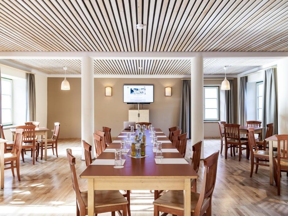 Sie sehen einen gut ausgestatteten Seminarraum mit TV und Fenstern im JUFA Hotel Murau. Der Ort für erfolgreiche und kreative Seminare in abwechslungsreichen Regionen.