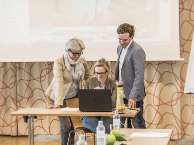 Zwei Seminarteilnehmer und die Seminarleiterin versammeln sich um einen Laptop im JUFA Hotel Wien City. Der Ort für erlebnisreichen Städtetrip für die ganze Familie und der ideale Platz für Ihr Seminar.