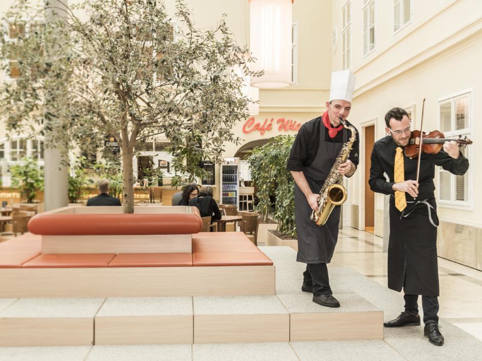 Zwei Sevicemitarbeiter des JUFA Hotels Wien City spielen im Atrium Saxophon und Geige. JUFA Hotels bietet erlebnisreichen Städtetrip für die ganze Familie.