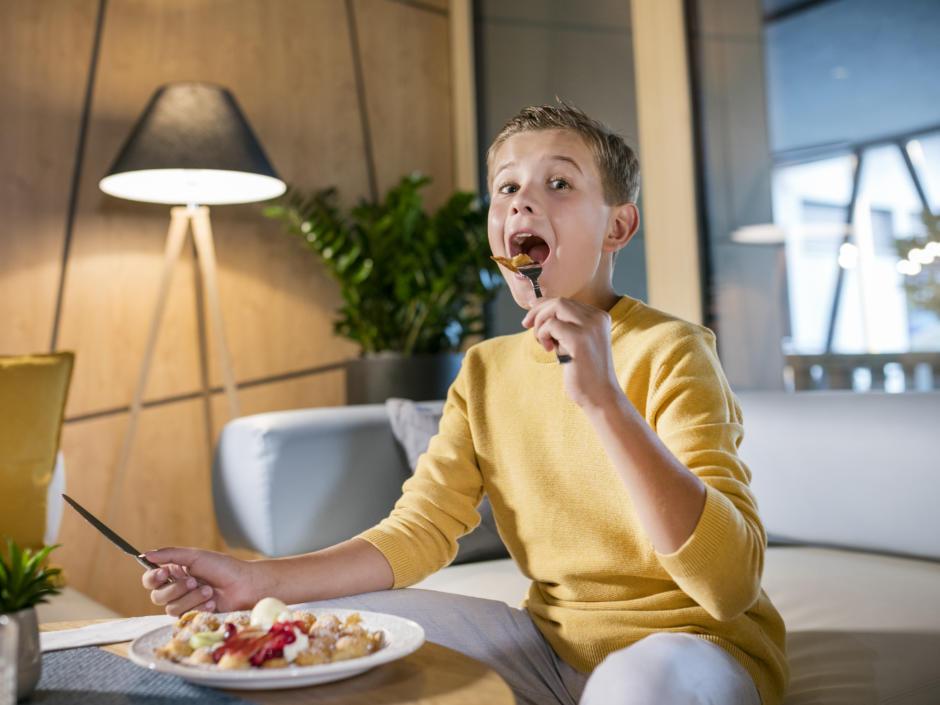 Sie sehen einen Jungen in einer Sitzecke eine Waffel essen im JUFA Hotel Weiz. Der Ort für kinderfreundlichen und erlebnisreichen Urlaub für die ganze Familie.