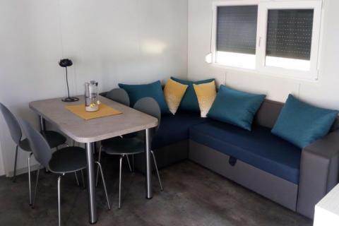Sie sehen eine gemütliche Sitzecke in einem Mobile Home am JUFA Vulkan Thermen-Resort mit einem Tisch. JUFA Hotels bietet erholsamen Thermenspass für die ganze Familie.