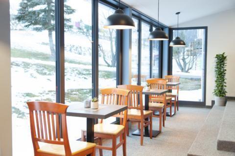 Sie sehen Sitzplätze am Fenster im Restaurant des JUFA Hotel Mariazell – Erlaufsee Sport-Resort. Der Ort für erfolgreiches Training in ungezwungener Atmosphäre für Vereine und Teams.
