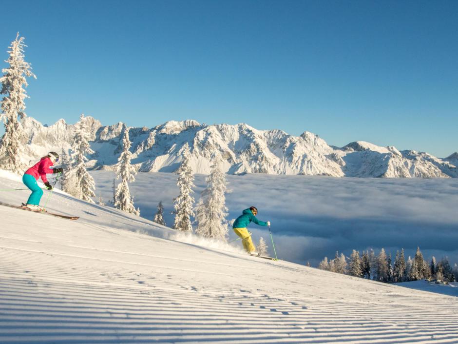 Sie sehen zwei Skifahrer am Hochwurzen in Schladming-Dachstein. JUFA Hotels bietet erholsamen Familienurlaub und einen unvergesslichen Winterurlaub.