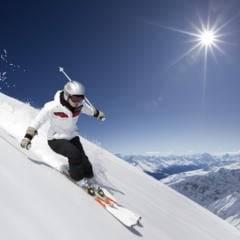 Skifahrer mit weisser Jacke beim Skifahren abseits der Piste in den Alpen. JUFA Hotels bietet erholsamen Familienurlaub und einen unvergesslichen Winterurlaub.