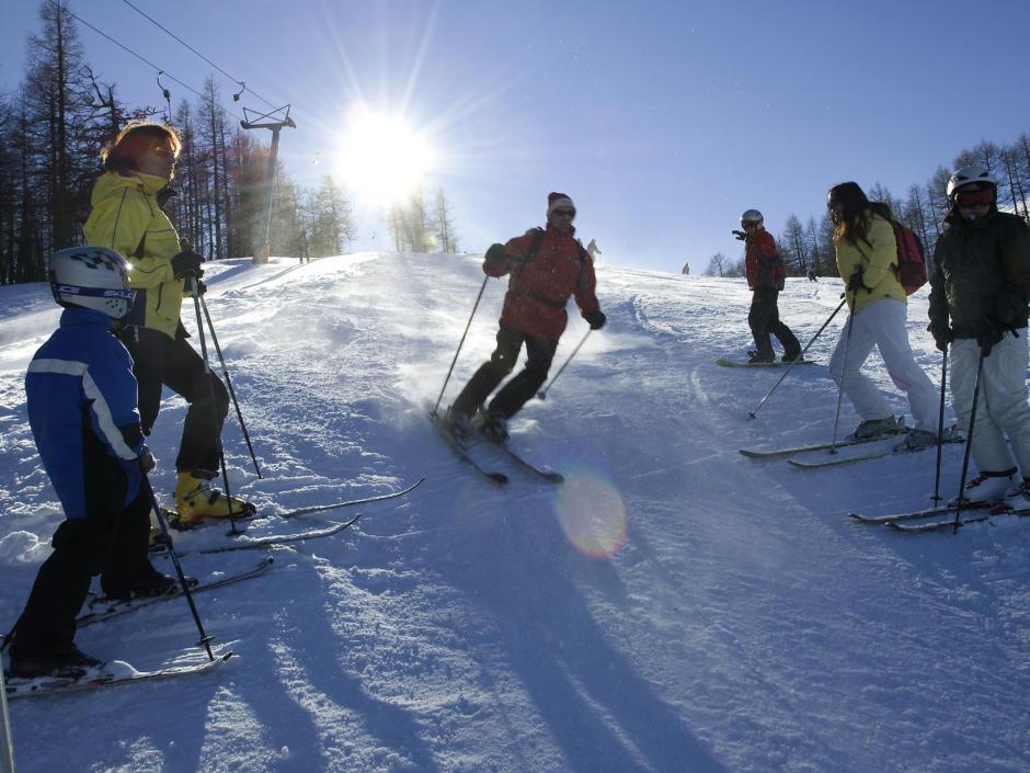 Sie sehen Skifahrer auf der Skipiste der Petzen im Winter. JUFA Hotels bietet erholsamen Familienurlaub und einen unvergesslichen Winterurlaub.