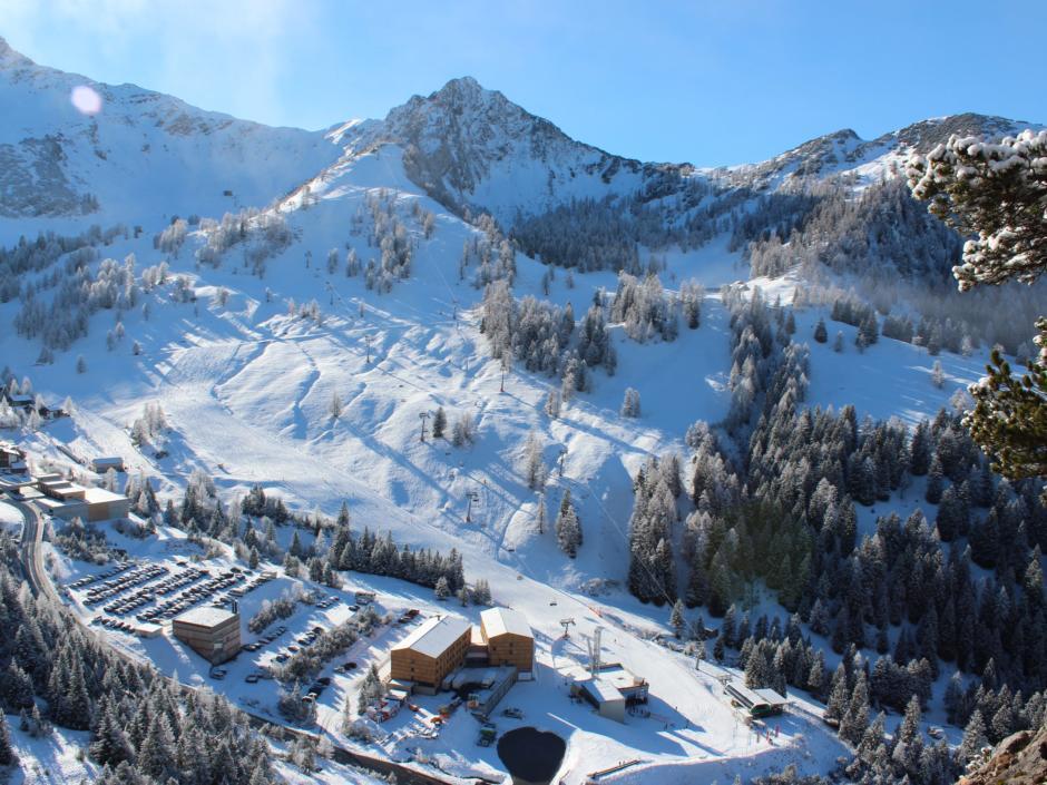 Sie sehen eine Landschaftsbild mit der Hotelansicht des JUFA Hotels Malbun Alpin-Resort aus der Vogelperspektive im Winter mit Schnee. Der Ort für erholsamen Familienurlaub und einen unvergesslichen Winter- und Wanderurlaub.