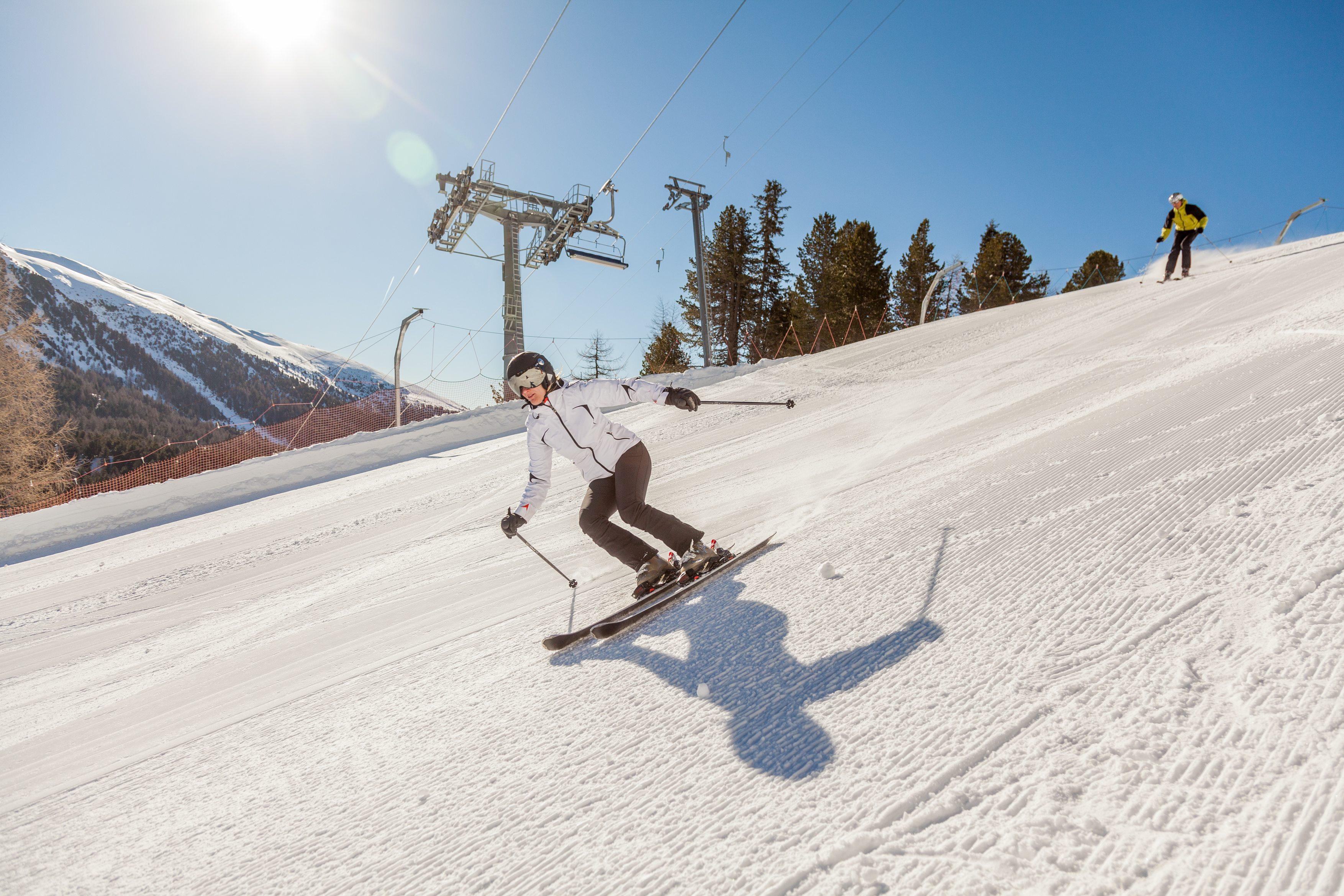 Eine Skifahrerin fährt gekonnt die bestens präparierte Piste im Skigebiet Turracher Höhe in Kärnten hinunter. JUFA Hotels bietet erholsamen Familienurlaub und einen unvergesslichen Winterurlaub.