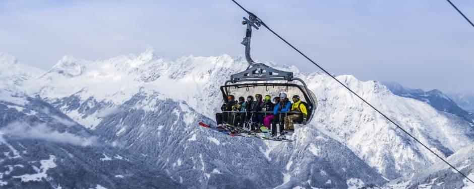 Sie sehen einen mit Skifahrern besetzten Skilift im Montafon. JUFA Hotels bietet erholsamen Familienurlaub und einen unvergesslichen Winterurlaub.