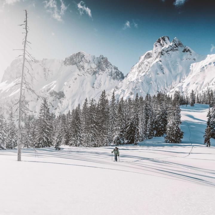 Sie sehen einen Skitourengeher in der Winterlandschaft des Nationalparks Gesäuse.