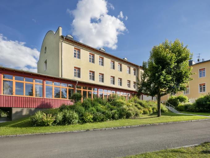 Sie sehen das JUFA Hotel Waldviertel aus Frontansicht im Sommer. Der Ort für erholsamen Familienurlaub und einen unvergesslichen Winter- und Wanderurlaub.