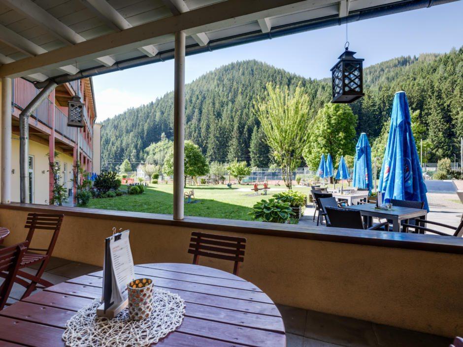Sie sehen die gemütliche Sonnenterrasse im JUFA Hotel Veitsch mit Blick auf Spielwiese. JUFA Hotels bietet kinderfreundlichen und erlebnisreichen Urlaub für die ganze Familie.