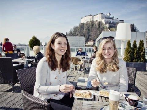 Freundinnen gnießen einen Kaffee und etwas Süßes auf der Sonnenterrasse im Unikum Sky by JUFA Hotels. JUFA Hotels bieten erholsamen Familienurlaub und einen unvergesslichen Winter- und Wanderurlaub.