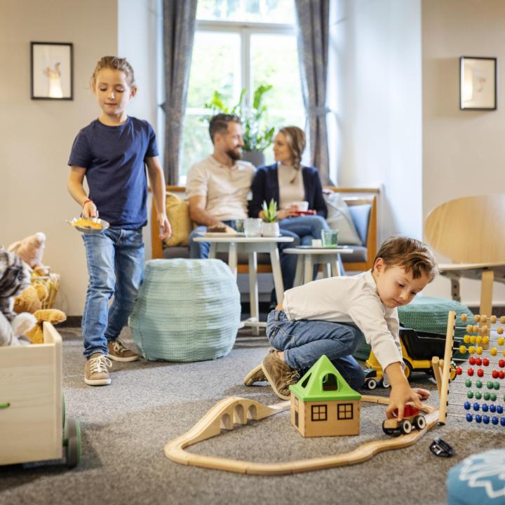 Sie sehen Kinder in der Spieleecke spielen, im Hintergrund sieht man die Eltern mit einem Kaffee an einem Tisch sitzen. JUFA Hotels bietet kinderfreundlichen und erlebnisreichen Urlaub für die ganze Familie.
