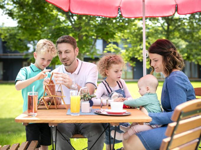 Sie sehen den Garten des JUFA Hotels Mariazell-Erlaufsee mit einer Familie beim Spielen und Getränken. JUFA Hotels bietet erholsamen Familienurlaub und einen unvergesslichen Winter- und Wanderurlaub.