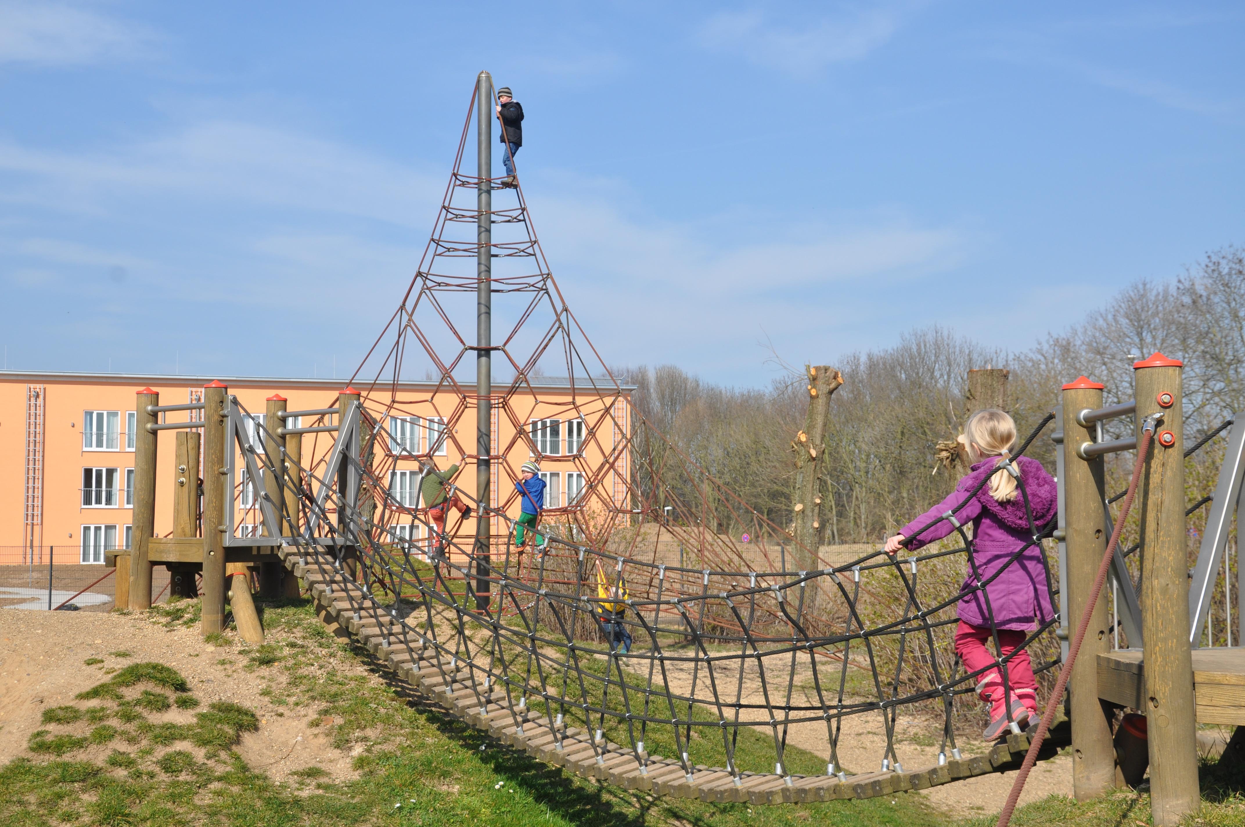 Kind geht über Hängebrücke am Spielplatz am JUFA Hotel Jülich. Der Ort für kinderfreundlichen und erlebnisreichen Urlaub für die ganze Familie.