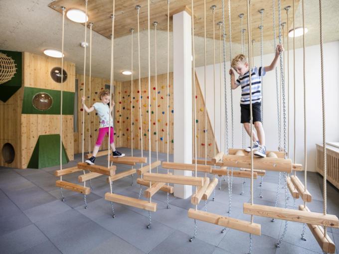 Sie sehen den Indoor Spielbereich mit Kinder beim Basteln, Klettern und Toben. JUFA Hotels bietet erholsamen Familienurlaub und einen unvergesslichen Winter- und Wanderurlaub.