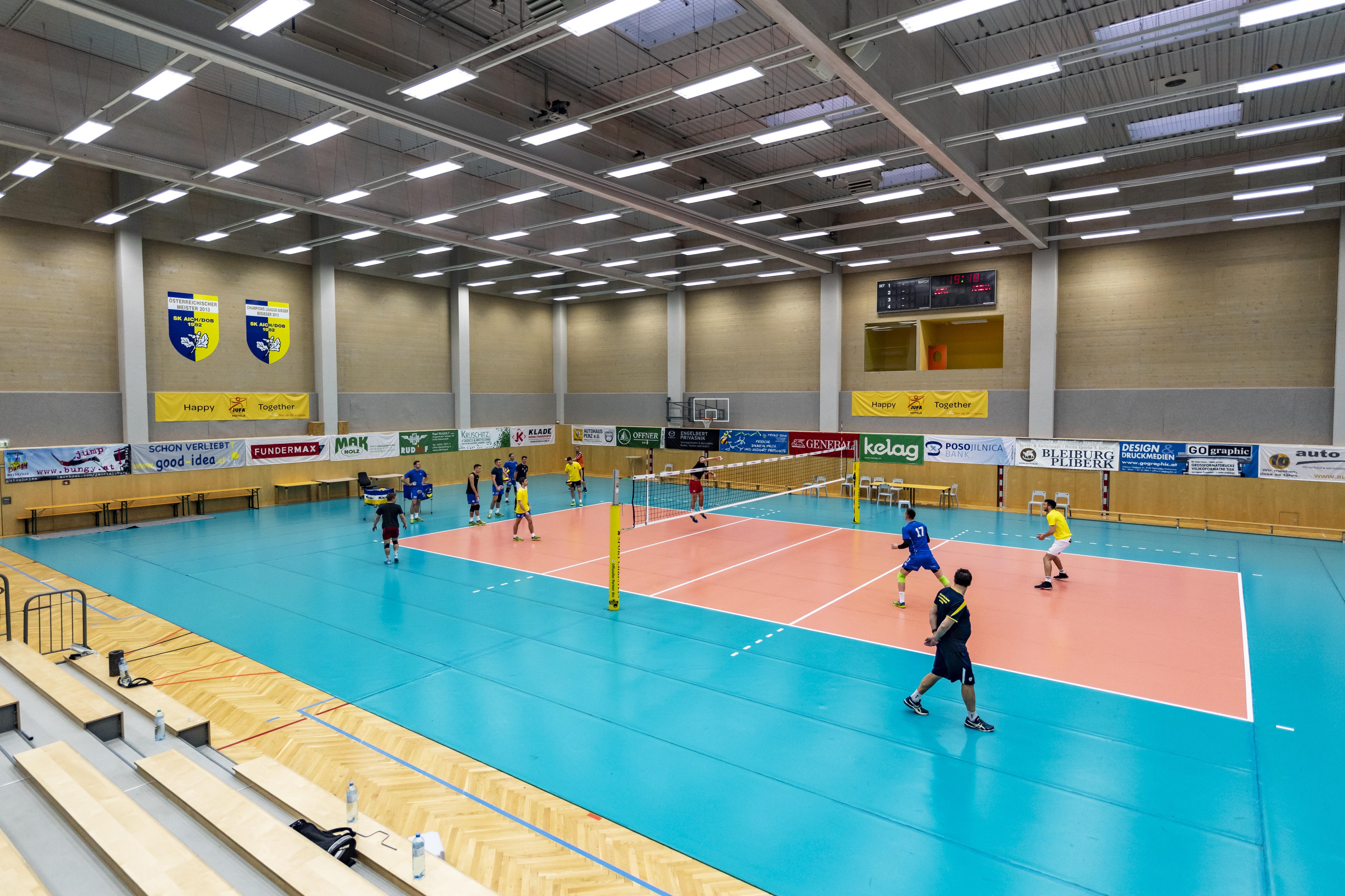 Sie sehen die Sporthalle beim JUFA Hotel Bleiburg/Pliberk – Sport-Resort mit einem Volleyballnetz. JUFA Hotels bietet Ihnen den Ort für erfolgreiches Training in ungezwungener Atmosphäre für Vereine und Teams.