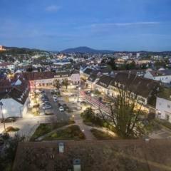 Sie sehen das Stadtzentrum von Weiz am Abend. JUFA Hotels bietet erholsamen Familienurlaub und einen unvergesslichen Winter- und Wanderurlaub.