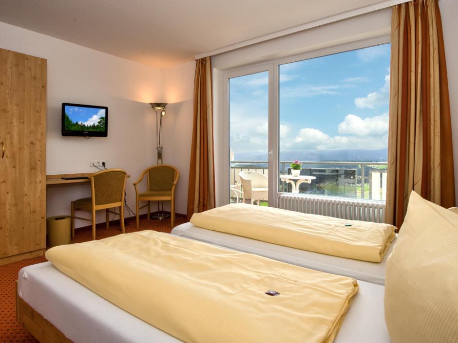 Sie sehen ein Doppelbett im Standard Doppelzimmer mit Balkon im JUFA Hotel Schwarzwald. Der Ort für erholsamen Familienurlaub und einen unvergesslichen Winterurlaub.