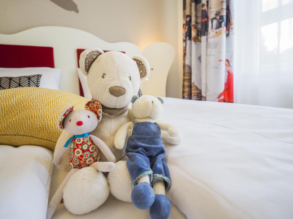 Sie sehen Stofftiere im Bett in einem FF4 Zimmer im JUFA Hotel Salzburg City. Der Ort für erholsamen Familienurlaub und einen unvergesslichen Winter- und Wanderurlaub.