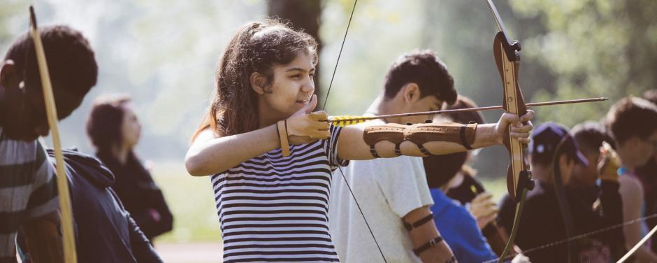 Sie sehen eine Gruppe von Stressless Instinct beim Bogenschießen im Park. JUFA Hotels bietet erlebnisreiche und kreative Schulprojektwochen in abwechslungsreichen Regionen.