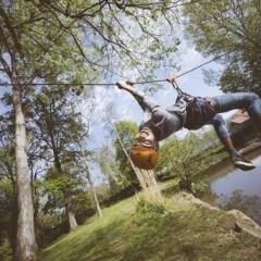 Sie sehen einen Jungen beim Überqueren eines Baches mittels einer Seilrutsche im Park. JUFA Hotels bietet erlebnisreiche und kreative Schulprojektwochen in abwechslungsreichen Regionen.