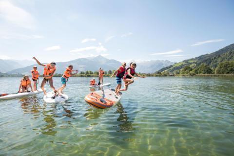 Sie sehen Kinder im Zeller See, die von einem SUP ins Wasser springen. JUFA Hotels bietet erholsamen Familienurlaub und einen unvergesslichen Wanderurlaub.