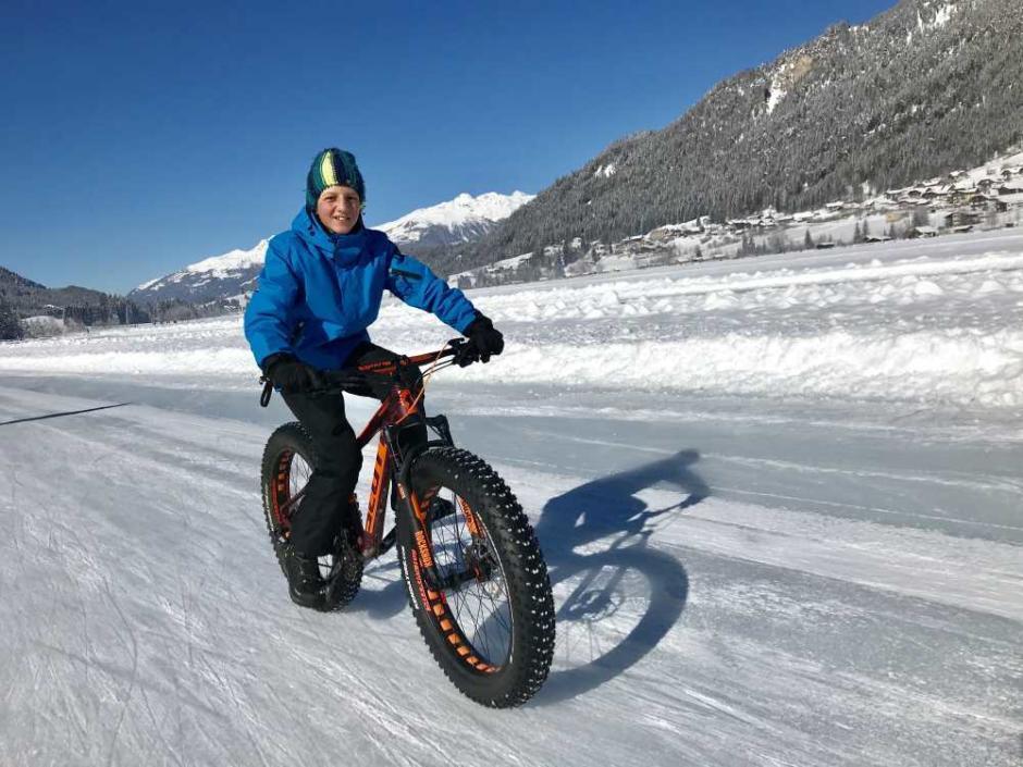 Sie sehen einen Teenager mit einem Fatbike auf dem vereisten Weissensee in Kärnten im Winter. JUFA Hotels bietet erholsamen Familienurlaub und einen unvergesslichen Winterurlaub.