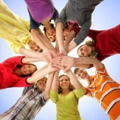 Teens bilden einen Kreis und legen ihre Hände übereinander als Zeichen für den Zusammenhalt in der Gruppe. JUFA Hotels bietet starkes und kreatives Teambuildung in abwechslungsreichen Regionen.