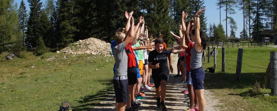 Teens bei einem Teamspiel in der Natur im Sommer. JUFA Hotels bieten erholsamen Familienurlaub und einen unvergesslichen Winter- und Wanderurlaub.