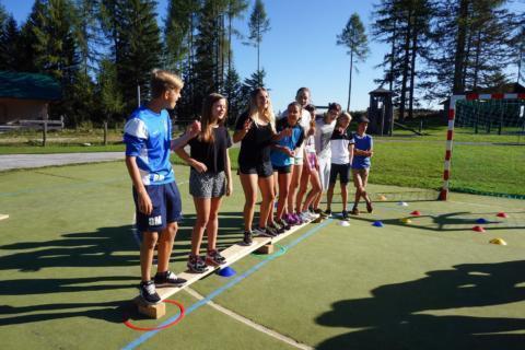Teens bei einem Teamspiel auf einem Sportplatz im Sommer. JUFA Hotels bieten erholsamen Familienurlaub und einen unvergesslichen Winter- und Wanderurlaub.