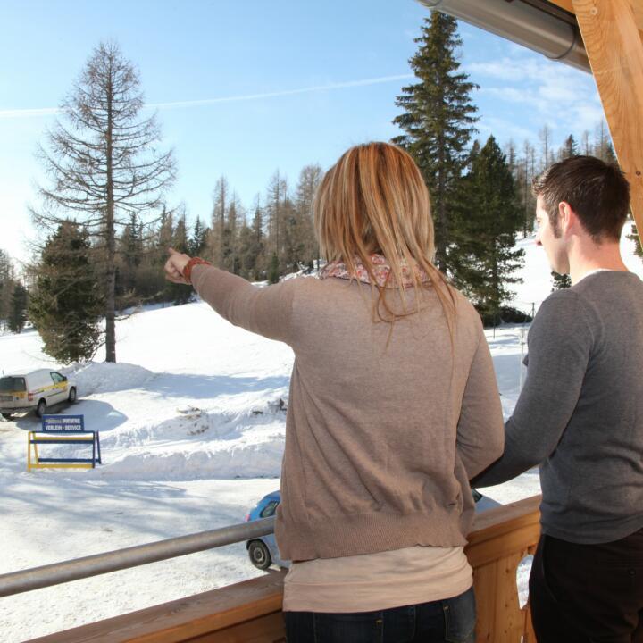 Sie sehen zwei Menschen auf der Terrasse eines Hotelzimmers mit Blick auf eine Winterlandschaft im JUFA Hotel Nockberge - Almerlebnis. Der Ort für erholsamen Familienurlaub und einen unvergesslichen Winter- und Wanderurlaub.
