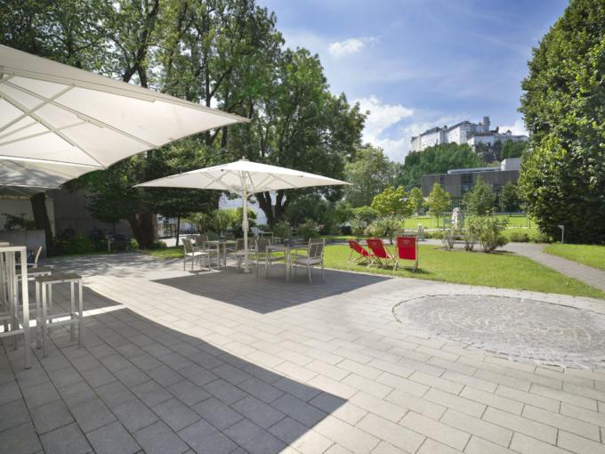 Sie sehen die Terrasse mit Gartenliege und Sonnenschirm im JUFA Hotel Salzburg City. Der Ort für erlebnisreichen Städtetrip für die ganze Familie und der ideale Platz für Ihr Seminar.