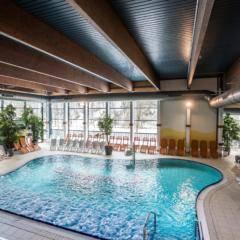 Sie sehen das Thayatal Vitalbad mit Relaxbecken und Liegestühlen im Waldviertel. JUFA Hotels bietet erholsamen Familienurlaub und einen unvergesslichen Winter- und Wanderurlaub.
