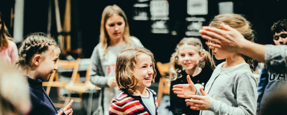 Sie sehen eine Gruppe Kinder bei der Theaterpädagogik auf der Bühne. JUFA Hotels bietet erlebnisreiche und kreative Schulprojektwochen in abwechslungsreichen Regionen.