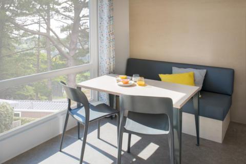 Sie sehen einen Tisch in einem Mobile Home beim JUFA Vulkan Thermen-Resort mit großem Fenster. JUFA Hotels bietet erholsamen Thermenspass für die ganze Familie.