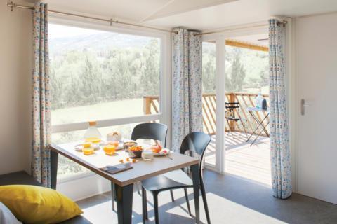 Sie sehen einen Tisch in einem Mobile Home beim JUFA Vulkan Thermen-Resort mit Frühstück. JUFA Hotels bietet erholsamen Thermenspass für die ganze Familie.