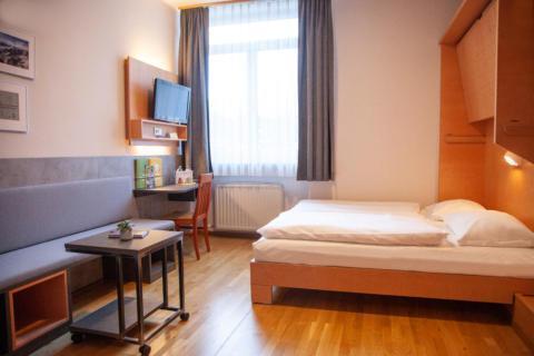 Sie sehen ein Familienzimmer FF4 mit TV, Fenster und Doppelbett im JUFA Hotel Kaprun. Der Ort für erholsamen Familienurlaub und einen unvergesslichen Winter- und Wanderurlaub.