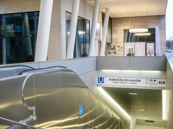 Sie sehen den Eingang zur U-Bahn Station HafenCity Universität vor dem JUFA Hotel Hamburg HafenCity. JUFA Hotels bietet kinderfreundlichen und erlebnisreichen Urlaub für die ganze Familie.