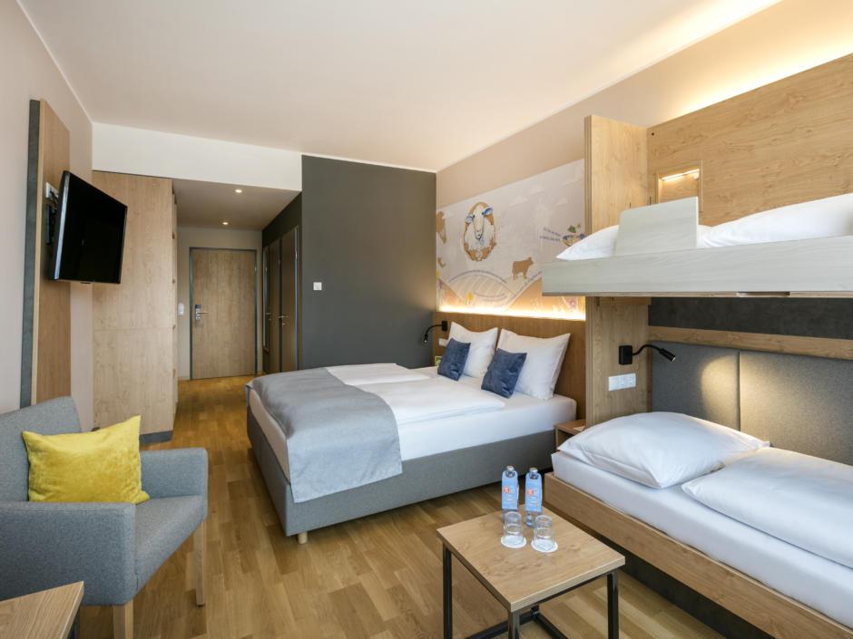 Sie sehen die Übersicht eines Familienzimmers FF4 mit Doppelbett und Etagenbett im JUFA Hotel Weiz. Der Ort für kinderfreundlichen und erlebnisreichen Urlaub für die ganze Familie.