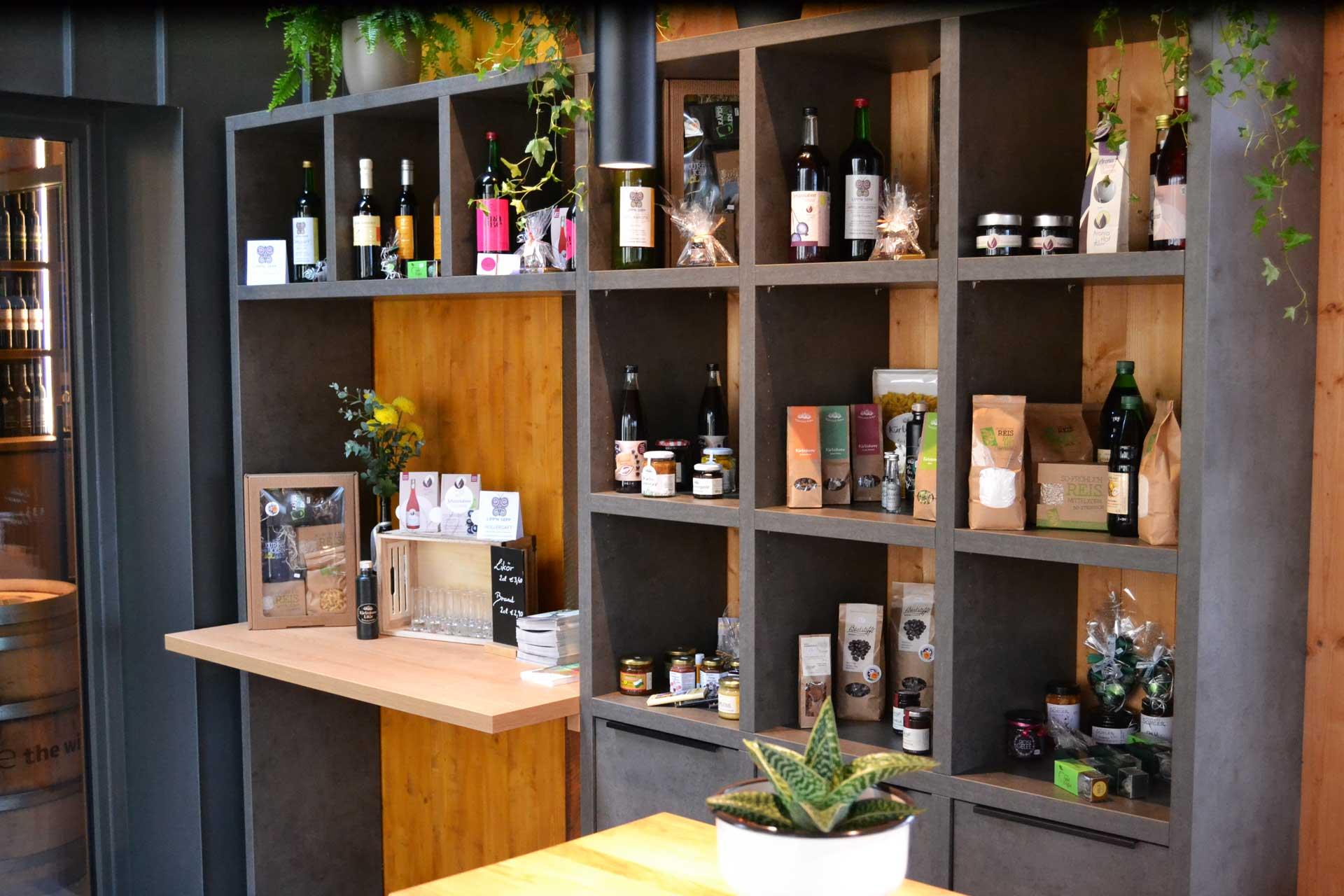 Sie sehen ein Regal mit Produkten aus dem Genussladen des JUFA Hotels Tieschen - Bio-Landerlebnis***. Der Ort für erlebnisreichen Natururlaub für die ganze Familie.