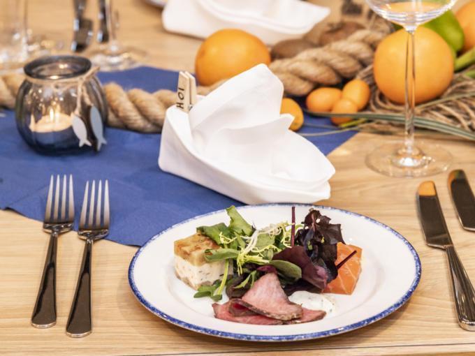 Sie sehen einen Vorspeisenteller im Restaurant des JUFA Hotel Hamburg HafenCity mit Salat, Fisch und Fleisch. JUFA Hotels bietet erlebnisreichen Städtetrip für die ganze Familie und den idealen Platz für Ihr Seminar.