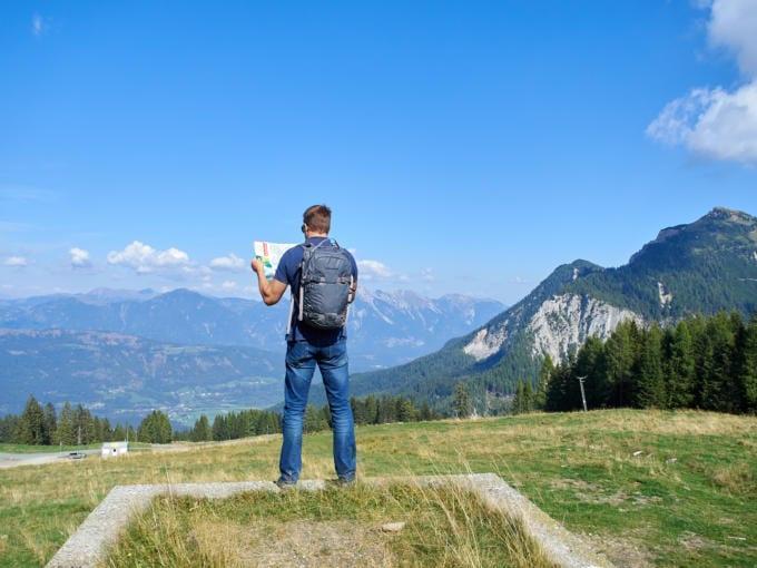 Sie sehen einen Mann mit Wanderkarte in Natur. JUFA Hotels bietet erholsamen Familienurlaub und einen unvergesslichen Wanderurlaub.